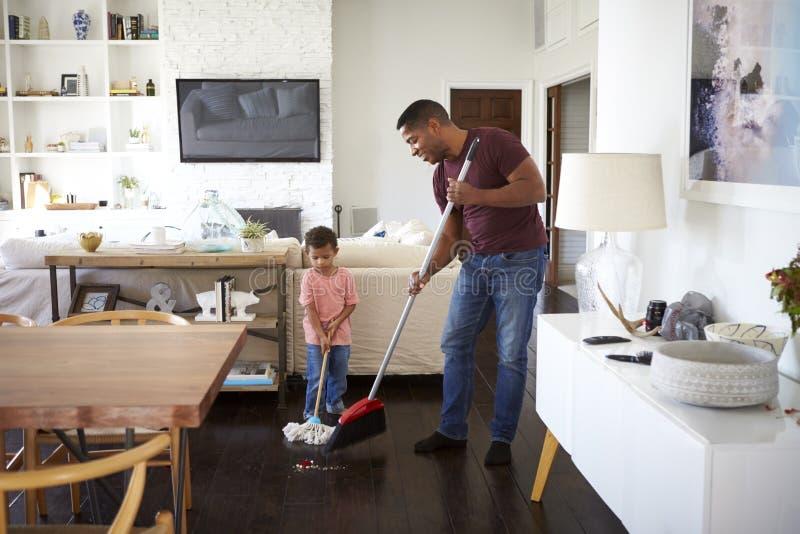 Дед и его годовалый внук 3 mopping и подметая пол столовой, во всю длину стоковое изображение rf