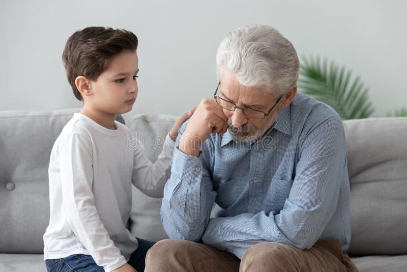 Дед комфорта мальчика расстроенный показывая поддержку и любовь стоковые фото