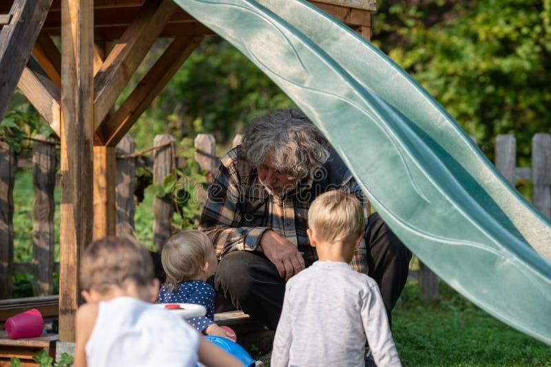 Дед сидя под скольжением играя с его внуками стоковое изображение