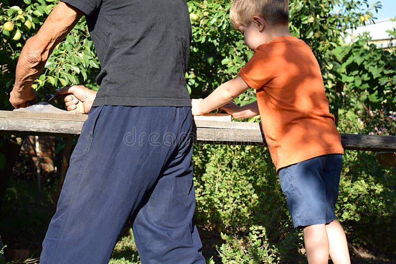 Дед с внуком строгая доску с planers руки стоковая фотография