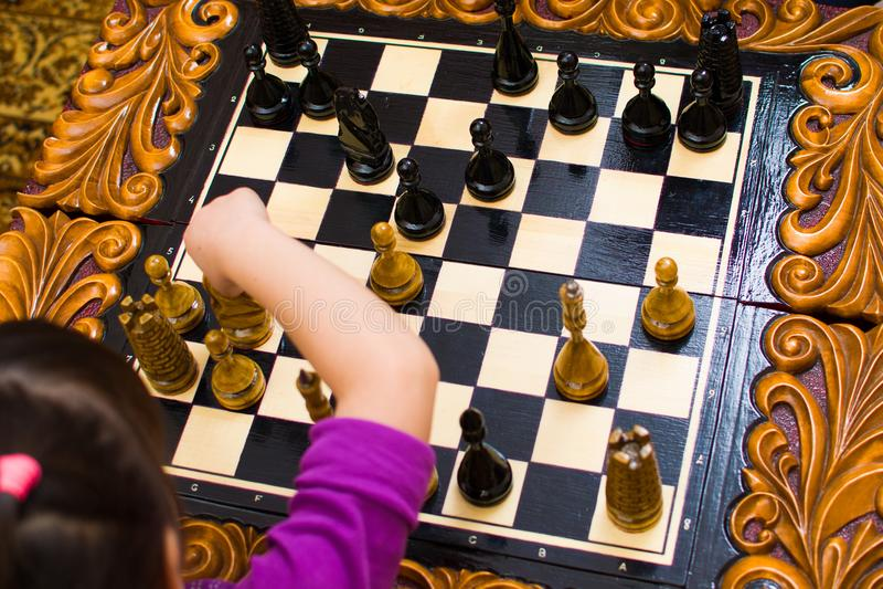 Дед учит шахмат для того чтобы сыграть для ее внучки стоковое изображение rf