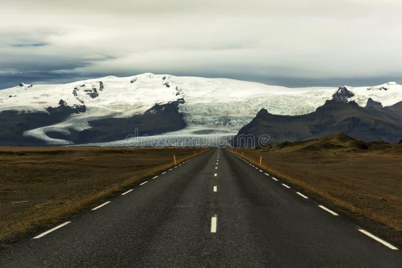 Дезертированная дорога асфальта прямая на предпосылке ледниковых гор Ландшафты Исландии Дух приключений и перемещение стоковые изображения