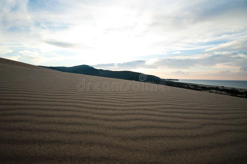 Дезертированный песчаный пляж с чистым точным песком на восходе солнца стоковые фото