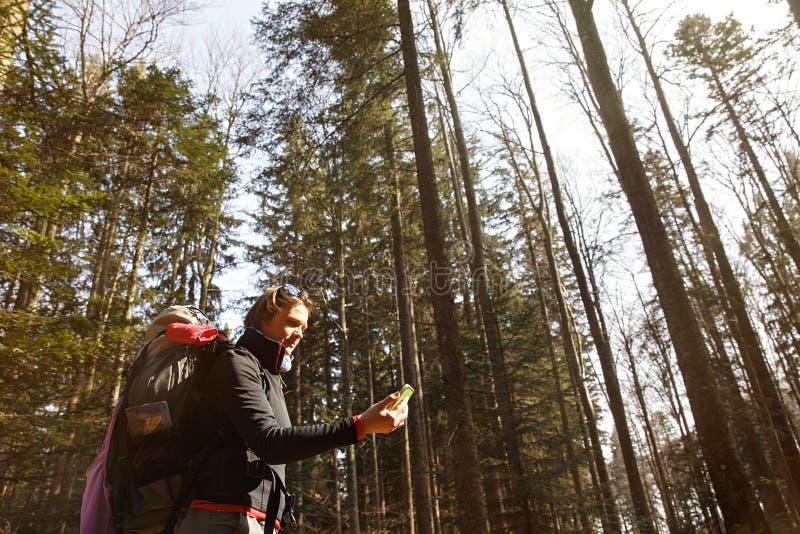 Дезориентированный hiker проверяя ее телефон для направления стоковые изображения