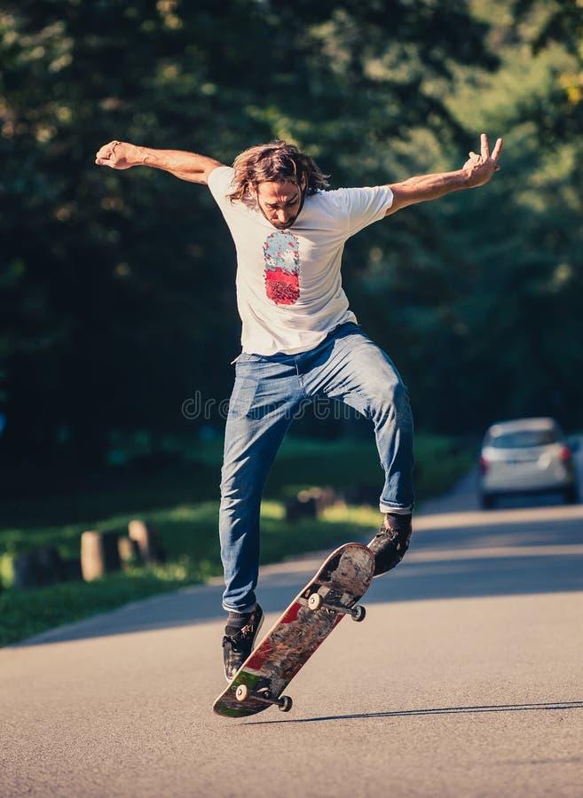 Действие сняло скейтбордиста катаясь на коньках, делающ фокусы и скакать стоковое фото rf