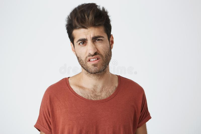 Действительно возмутительный стильный мальчик с ультрамодной стрижкой одел в вскользь одежде стоя на белой стене студии, выражая стоковые изображения