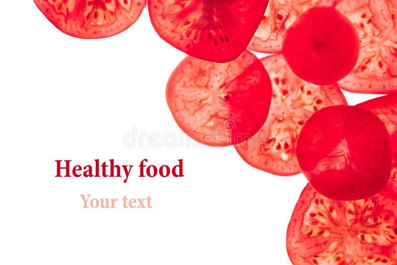 Декоративная рамка кусков томатов на белой предпосылке изолировано Круги отрезанные томатами Рамка, граница от овощей стоковое фото
