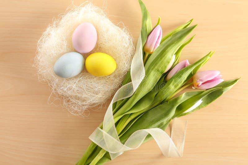 Декоративное гнездо с покрашенными пасхальными яйцами и цветками весны на таблице стоковые изображения rf