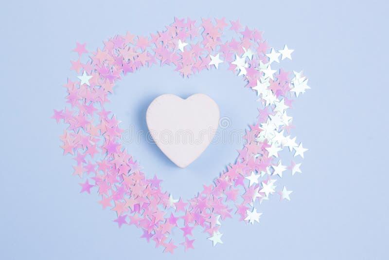 Декоративное деревянное сердце с розовыми яркими блесками на пастельной голубой предпосылке стоковые фотографии rf