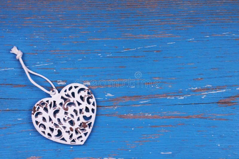 Декоративное металлическое сердце на голубой предпосылке стоковое изображение