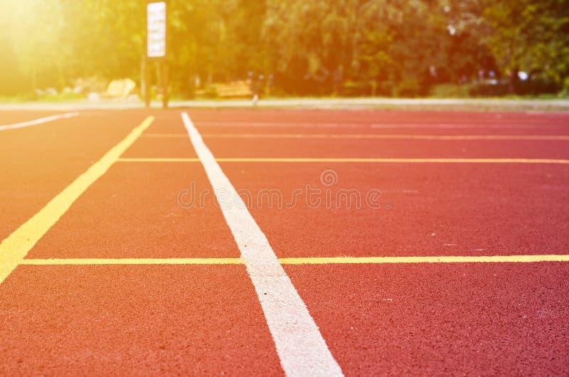 Декоративное прорезиновое Jogging покрытие на стадионе улицы в внешнем с белой линией Предпосылка спорта с влиянием солнечного св стоковые изображения rf