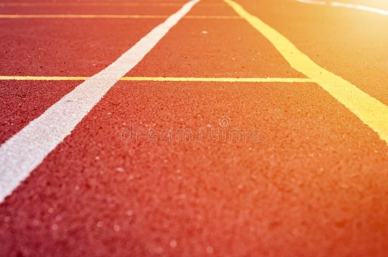Декоративное прорезиновое Jogging покрытие на стадионе улицы в внешнем с белой линией Предпосылка спорта с влиянием солнечного св стоковая фотография rf