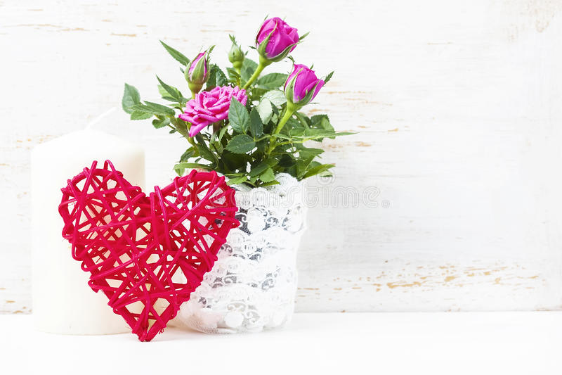 Декоративное сердце, розовые розы и свечи на белом деревянном backgro стоковые изображения