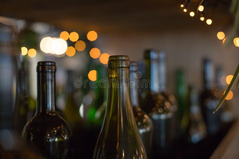 Декоративные внутренние элемент-темные стеклянные пустые бутылки на сияющей предпосылке Много стеклянных бутылок вина как оформле стоковое фото rf