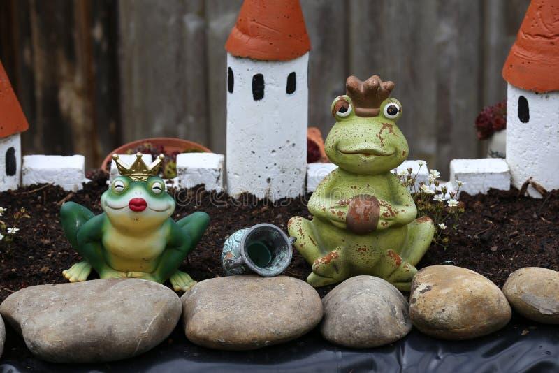 Декоративные лягушки стоят около пруда сада стоковые фото