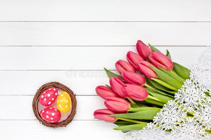 Декоративные пасхальные яйца в гнезде и красные тюльпаны на белом деревянном столе Скопируйте космос, взгляд сверху Декоративные  стоковая фотография rf