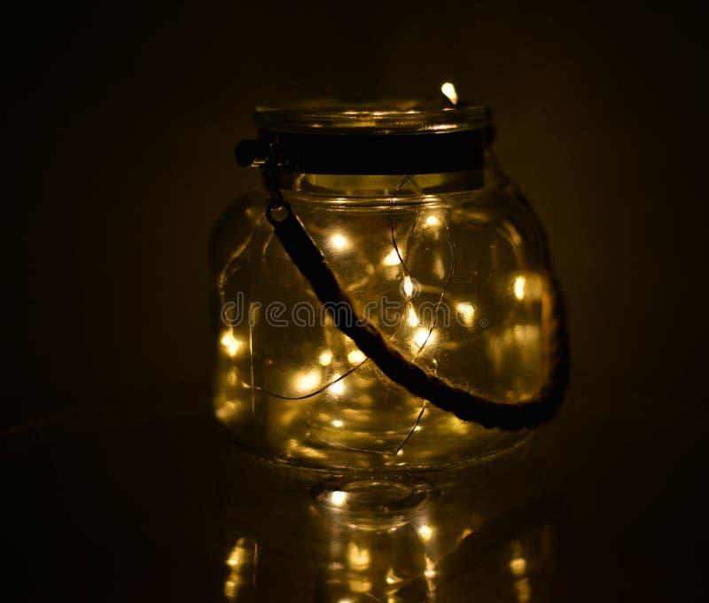 Декоративные света в стеклянном опарнике на темной комнате с влиянием зеркала на темной предпосылке украшения праздничные стоковая фотография