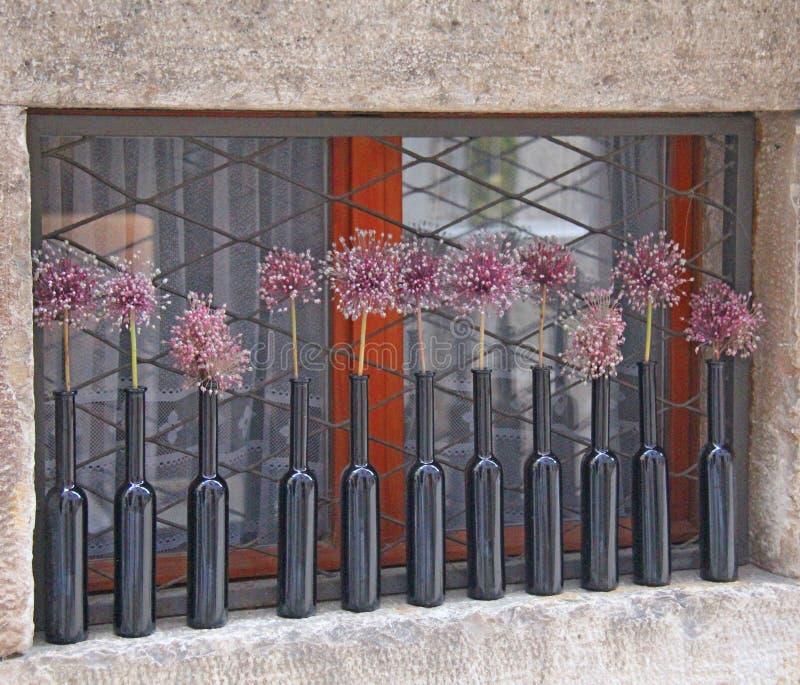 Декоративные стеклянные бутылки стоят на окне с цветками стоковое фото rf