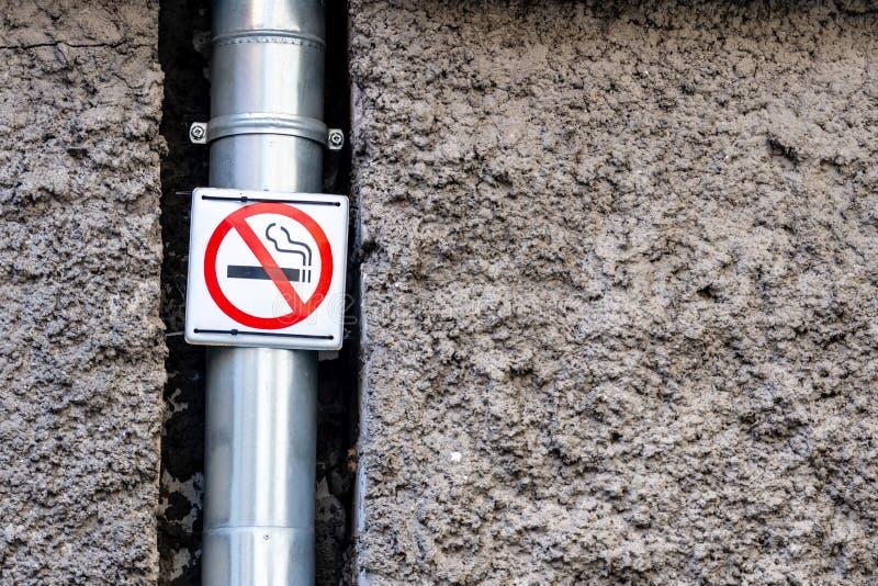 Декоративный гипсолит внешней стены с выбитой поверхностью Сточная канава металла Знак запрещая курение r стоковые изображения