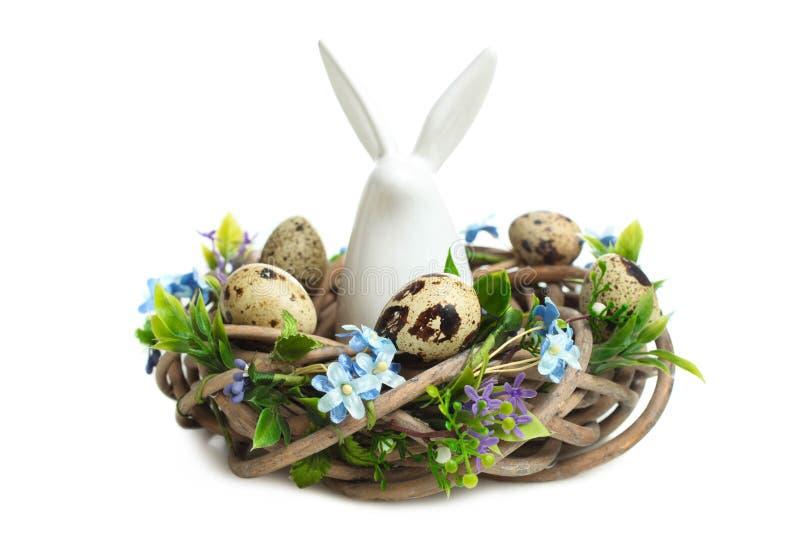 Декоративный зайчик пасхи сидя в гнезде с яйцами триперсток стоковые фотографии rf