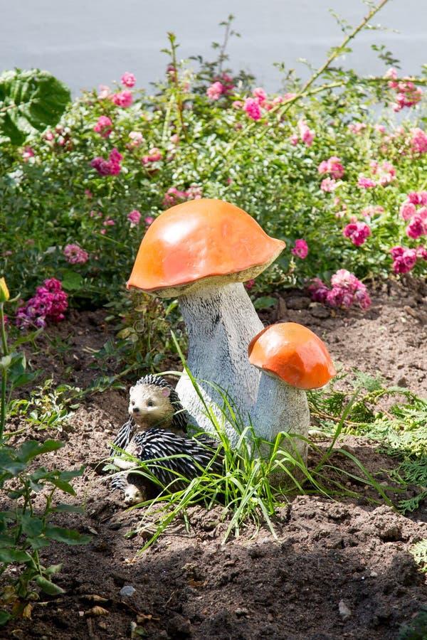 Декоративный керамический гриб с ежом на предпосылке цвета зеленой травы стоковое изображение