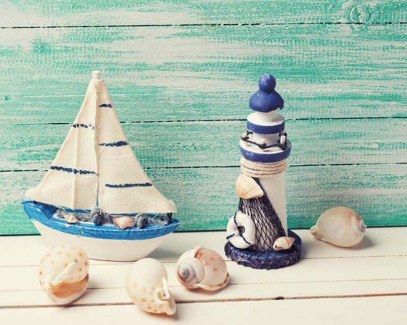 Декоративный маяк, парусник и морские детали на деревянном стоковое фото rf