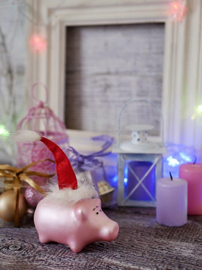 Декоративный сезонный состав игрушки свиньи Нового Года в красной шляпе Санта, праздничное освещение, свечи стоковая фотография