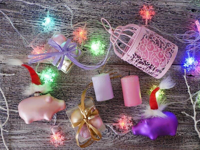 Декоративный сезонный состав поросят игрушки рождества в шляпах Санта красных, праздничное освещение стоковые изображения