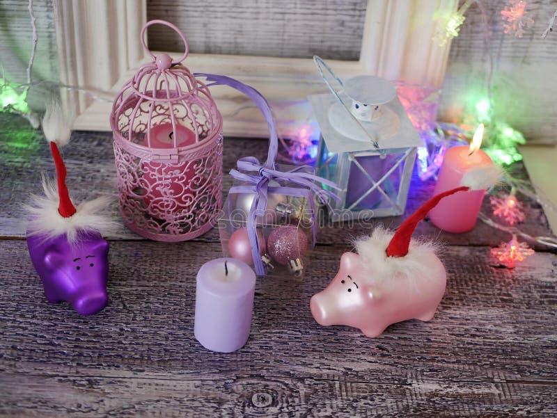 Декоративный сезонный состав поросят Нового Года игрушки в красных шляпах Санта, праздничное освещение, освещенное свечи стоковое фото rf