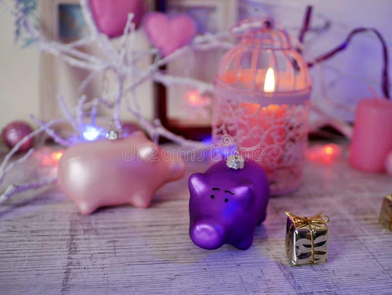 Декоративный состав пары украшений рождества свиней, горящих свечей, праздничных освещений, сердец войлока, agai шариков стоковые фотографии rf