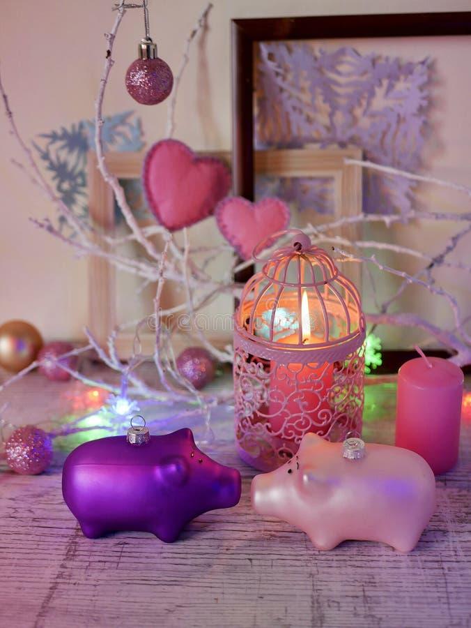 Декоративный состав пары украшений рождества свиней, горящих свечей, праздничных освещений, сердец войлока, agai шариков стоковые изображения rf