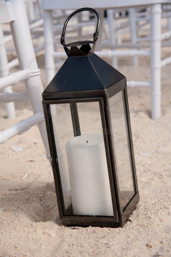 Декоративный фонарик свечи на песчаном пляже стоковые изображения