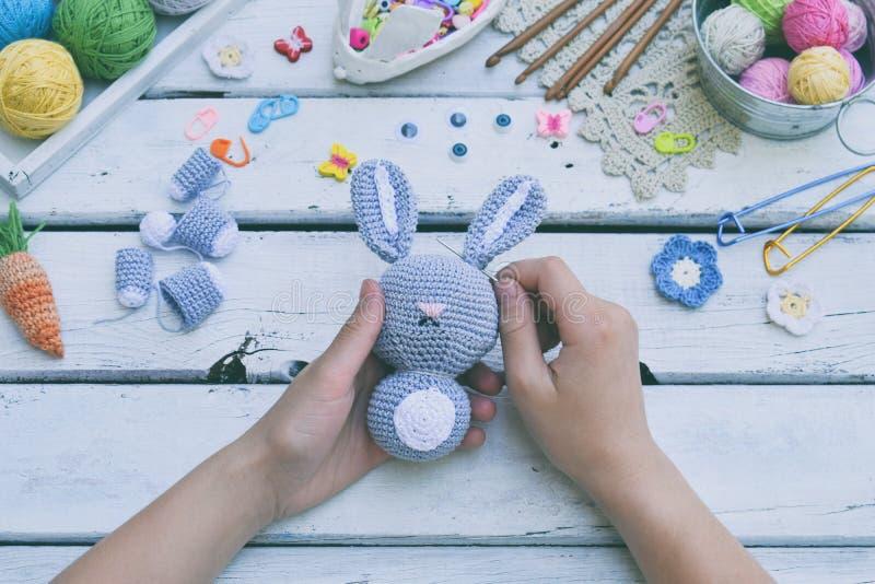Делать кролика с морковью Зайчик вязания крючком для ребенка На таблице продевает нитку, иглы, крюк, хлопчатобумажная пряжа Разде стоковое изображение rf