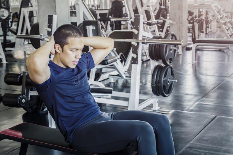 Делать молодого человека сидеть-поднимает на стенде стоковое фото rf