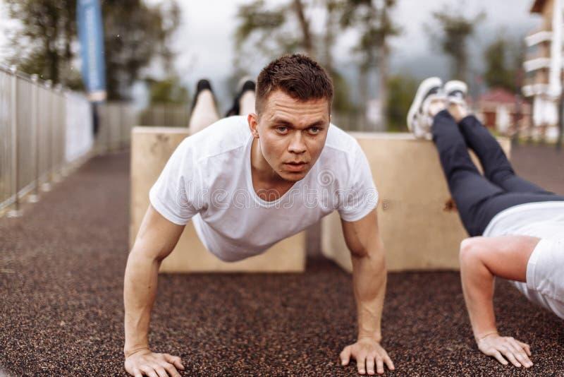 Делать 2 молодой спортсменов нажим-поднимает outdoors стоковые изображения rf