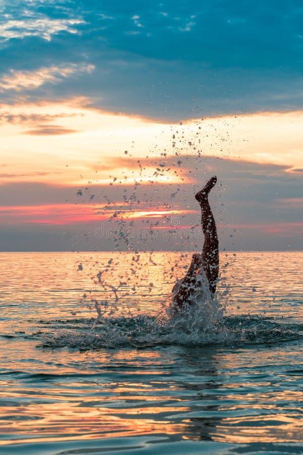 Делать пикирование в воду под заходом солнца стоковое изображение rf