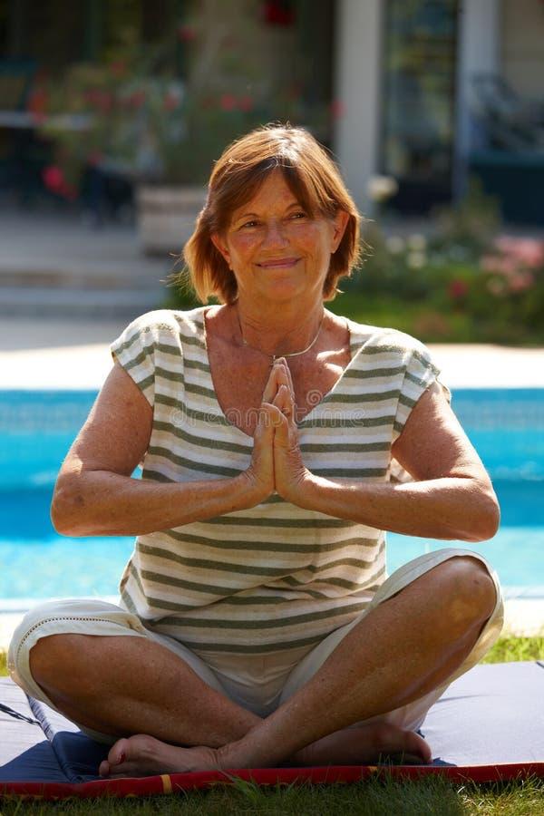 делать старшую йогу женщины стоковая фотография