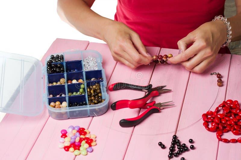 Делать ювелирных изделий Делать браслет красочных шариков Женские руки с инструментом на пинке стоковые изображения rf