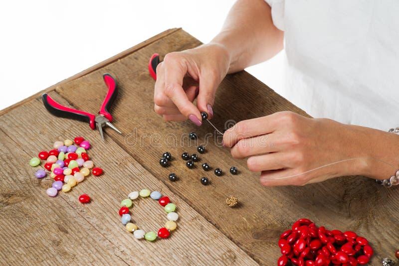 Делать ювелирных изделий Делать браслет красочных шариков Женские руки с инструментом на грубом деревянном столе стоковая фотография rf