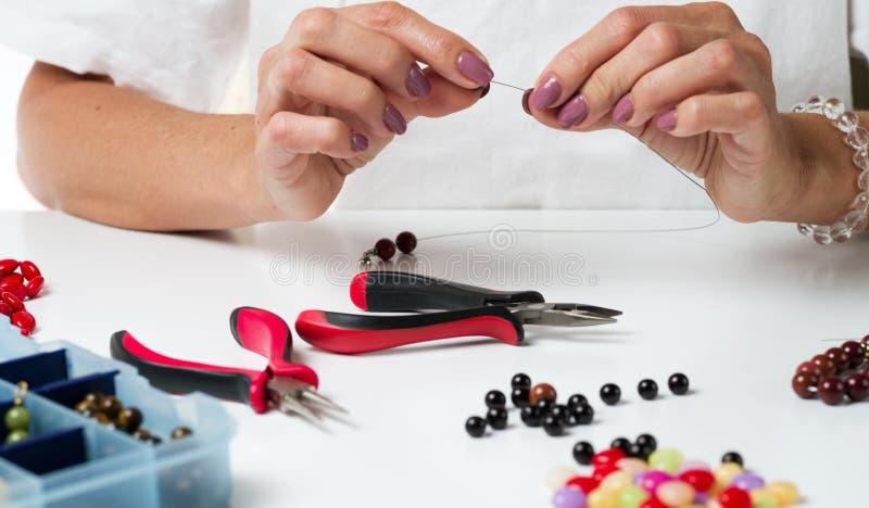 Делать ювелирных изделий Делать браслет красочных шариков Женские руки с инструментом стоковые фото