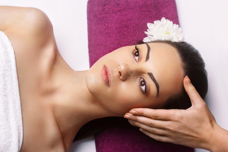 Делать Masseur массажирует голову женщины в салоне спа r Косметология, забота тела стоковое фото