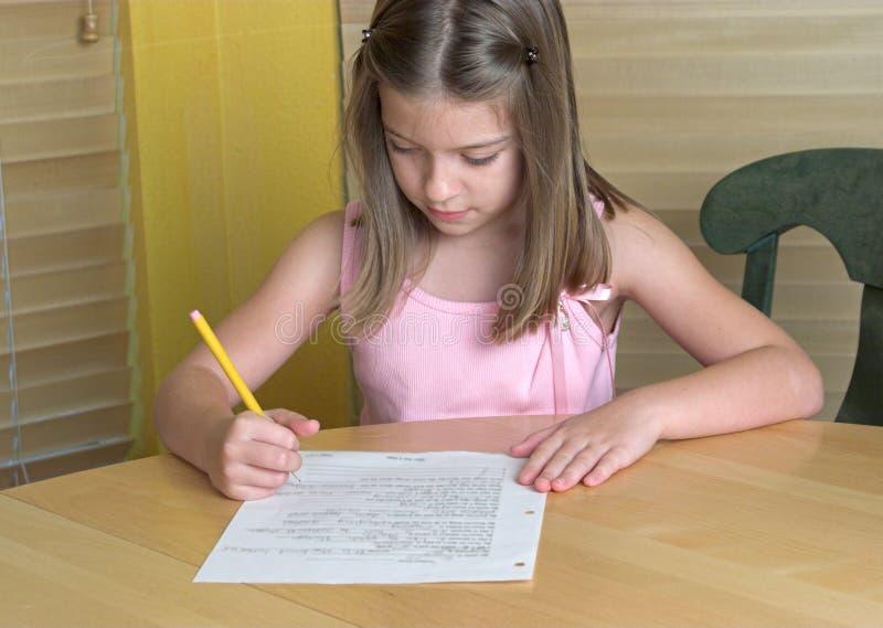 делающ домашнюю работу девушки немного стоковая фотография