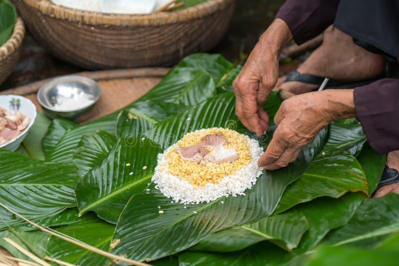 Делающ оборачивать торт Chung, въетнамскую лунную еду Tet Нового Года внешнюю с руками старухи и ингридиенты закрытый-вверх стоковые фото