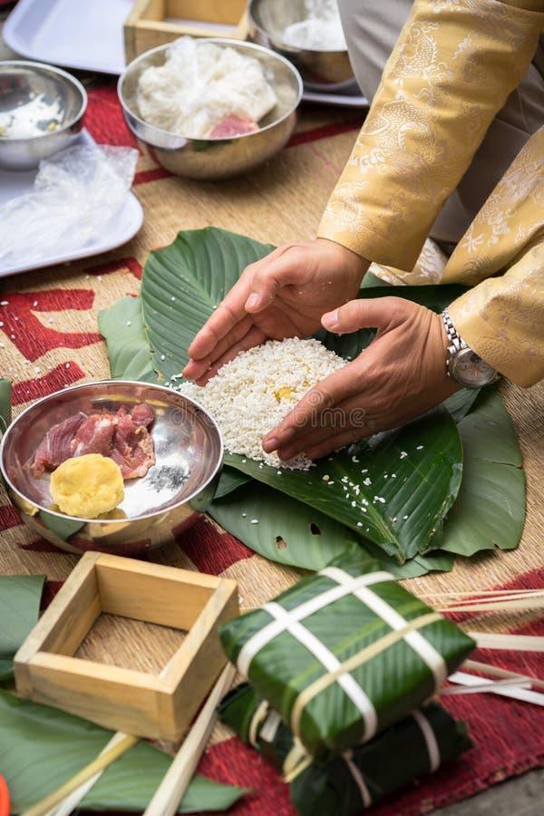 Делающ Chung испечь руками крупным планом, торт Chung самая важная традиционная въетнамская лунная еда Tet Нового Года стоковое изображение