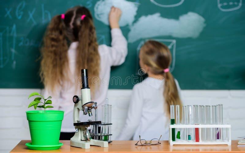 Дела науки Класс школы лаборатории Ребята школьного возраста в классе науки Микроскоп и лабораторное оборудование стоковая фотография