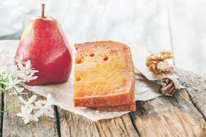 Деликатесы, пряные сыры Красный чеддер, на красивой текстурированной деревянной предпосылке с грушей смачная закуска для гурманов стоковое фото
