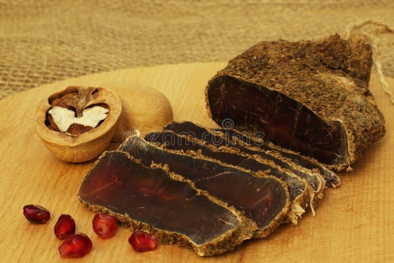 деликатность Очень вкусное душистое аппетитное пряное высушенное посоленное мясо со специями с красными семенами и грецкими ореха стоковая фотография