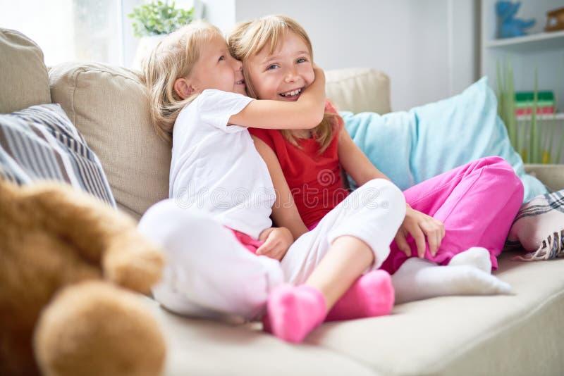 Делить секрет с милой сестрой стоковая фотография