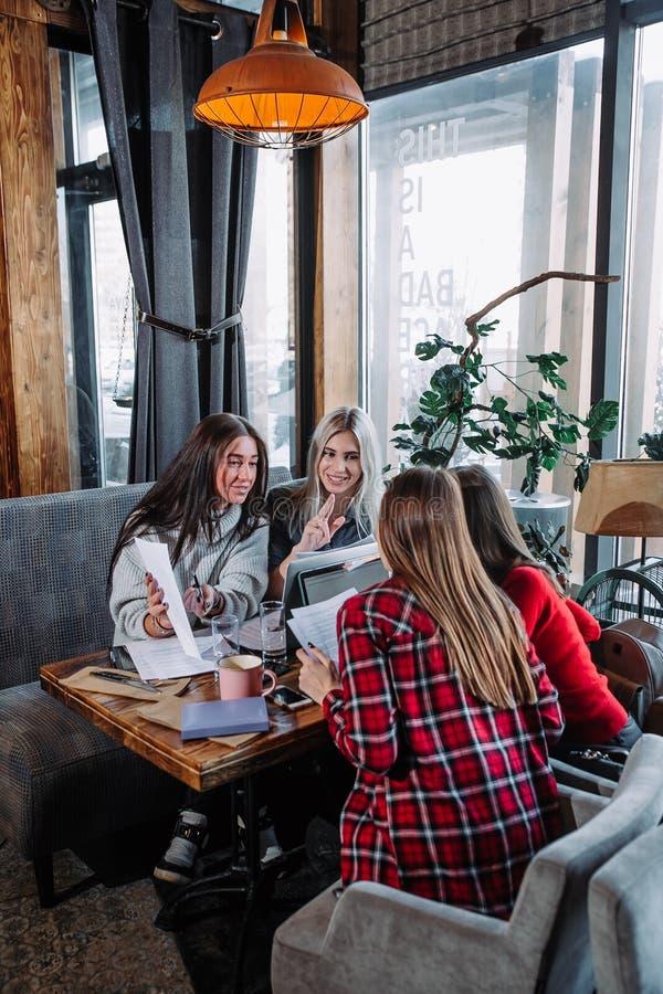 Деловая встреча в кафе, 4 молодой женщины сидя на таблице и обсуждая документы стоковые изображения