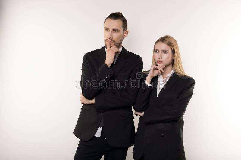 2 делового партнера в черных костюмах, красивого бородатого человек и красивая белокурая женщина думающ о разрешать стоковое фото rf